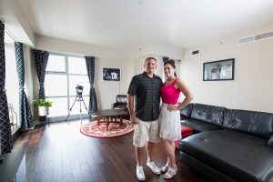 Happy couple standing in their living room of their home at The Ogden