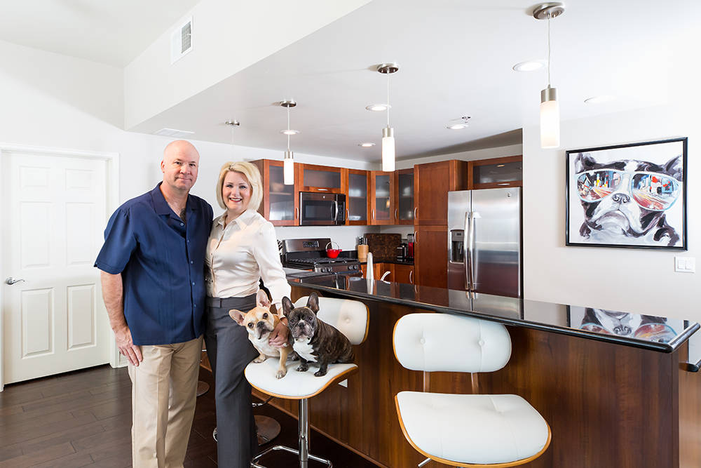 Couple with their dogs, standing in their kitchen in their home at The Ogden