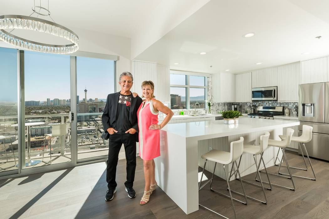 John and Robin standing in their kitchen in their home at The Ogden with their windows overlooking the Strip