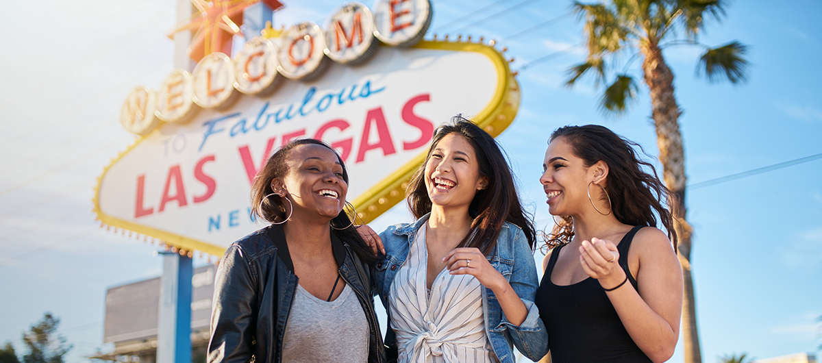 Three girlfriends laughing and smiling in front of the Welcome to Fabulous Las Vegas sign