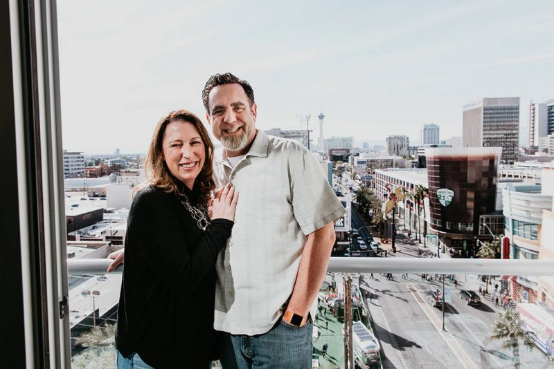 Happy couple standing on their balcony of their home at The Ogden overlooking the Fremont Street Experience
