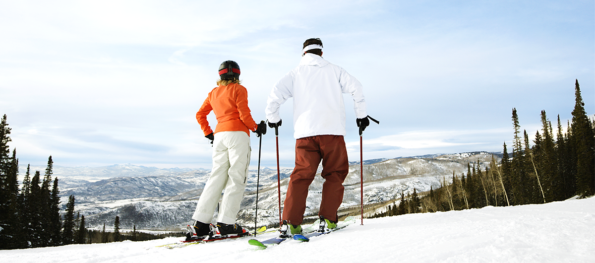 Couple at the stop of a mountain getting ready to ski down
